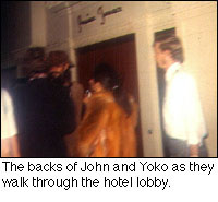 The backs of John and Yoko as they walk through the hotel lobby.